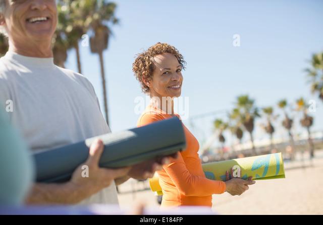 Portrait von lächelnden Frau mit Yoga-Matte am Strand Stockbild