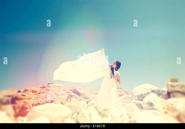 Frau in weiß auf einem Berggipfel. Stockbild