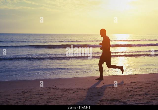gesunder Lebensstil, Silhouette der Läufer am Strand Stockbild