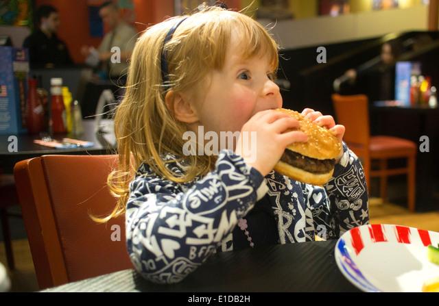 Vier 4 Jahre altes Mädchen im Restaurant essen Käse burger Stockbild