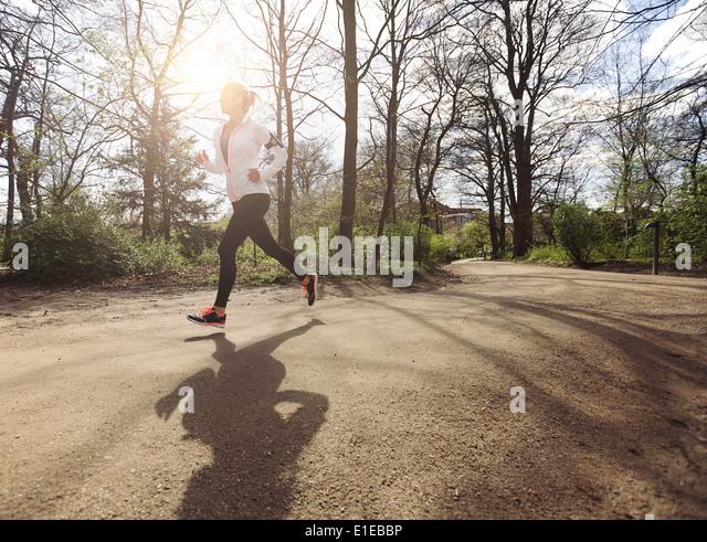 Gesunde junge Frau im Park Joggen. Fitness weibliches Modell in Wald laufen. Kaukasische Fitness-Modell Bewegung Stockbild