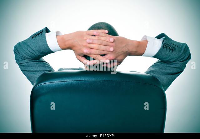 ein Geschäftsmann entspannende unter dem Vorsitz seines Amtes mit den Händen hinter dem Kopf Stockbild
