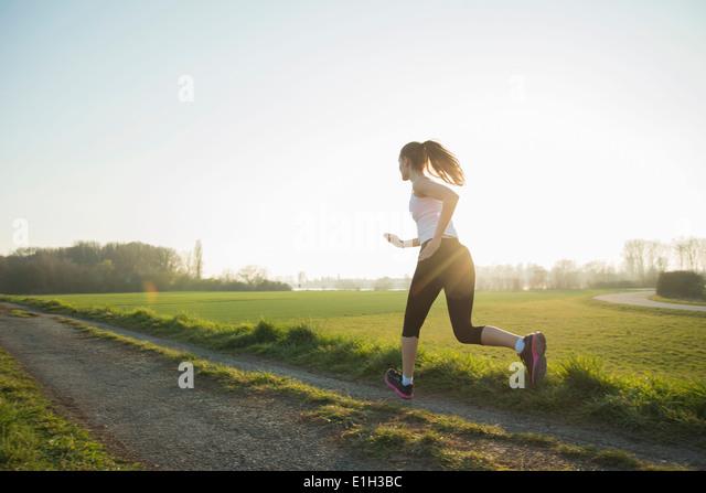 Junge weibliche Läufer auf Feldweg Stockbild