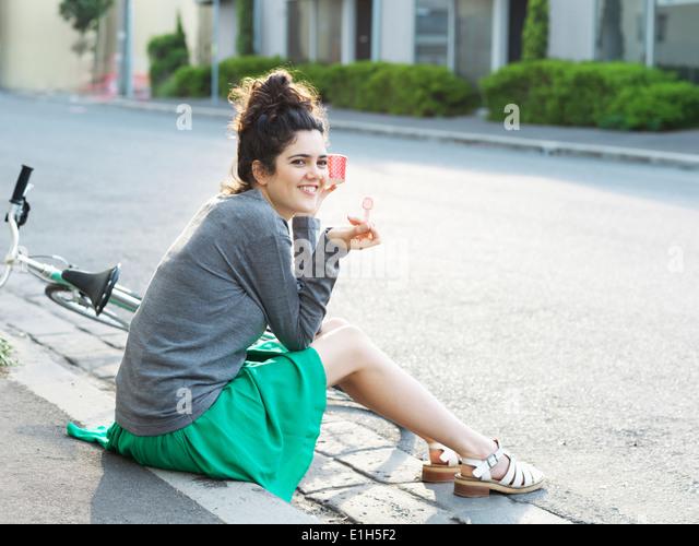 Porträt der jungen Frau auf Bürgersteig Eis essen Stockbild