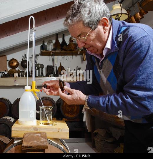 Mann macht und kümmert sich um über Balsamico Essig Aceto Balsamico Tradizionale di Modena Stockbild