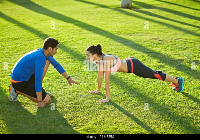 Personal Trainer mit Frau Plank Übung Stockbild