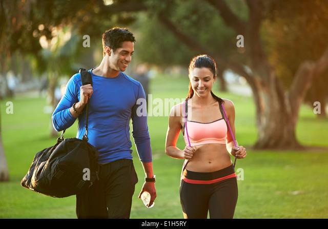 Mann und Frau tragen Sportkleidung zu Fuß durch den park Stockbild