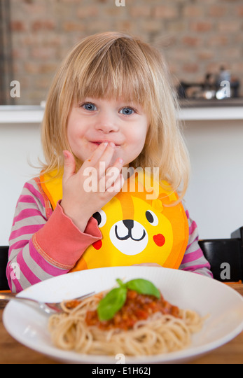 Porträt von 2 Jahre altes Mädchen essen Spaghetti mit Fingern Stockbild