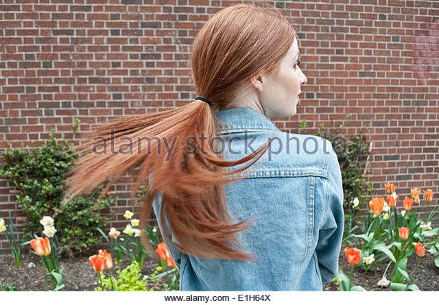Rückansicht des jungen Frau Spinning Pferdeschwanz Stockbild