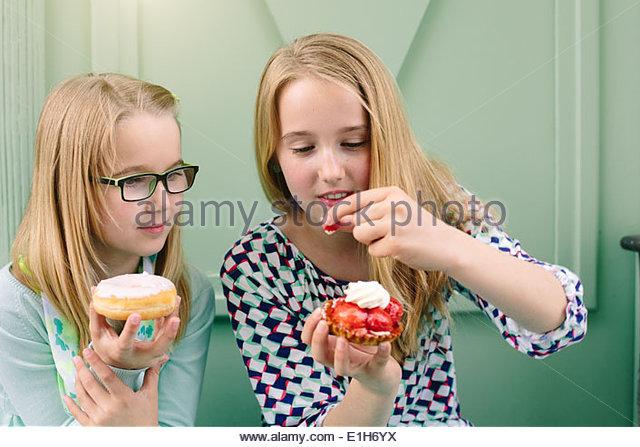Zwei Schwestern, die Abhaltung von Kuchen und Erdbeere Stockbild