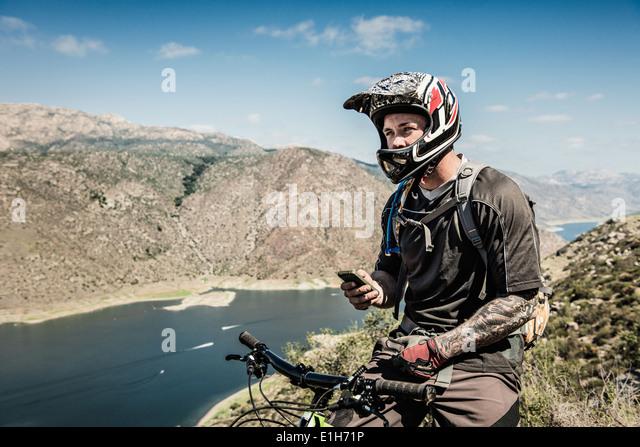 Downhill Mountainbiker mit smartphone Stockbild