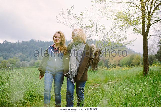 Reife Frau und Tochter im Teenageralter einen Spaziergang im Feld Stockbild