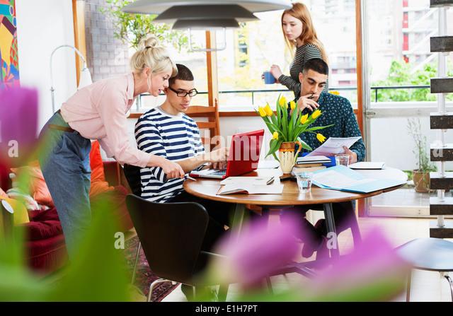 Vier junge Erwachsene sitzen um die Tabelle zu studieren Stockbild