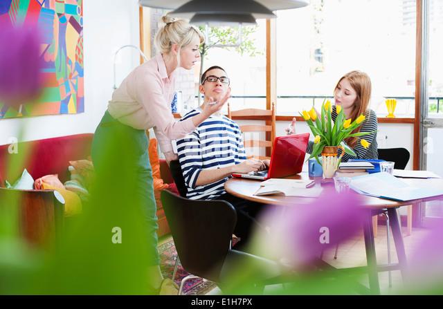 Junge Erwachsene, die herumsitzen und Studium der Tabelle Stockbild