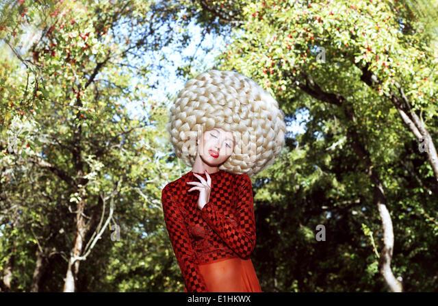 Außergewöhnliche Frisur. Frau in prächtigen Kunst Perücke mit gewellten Haaren Stockbild