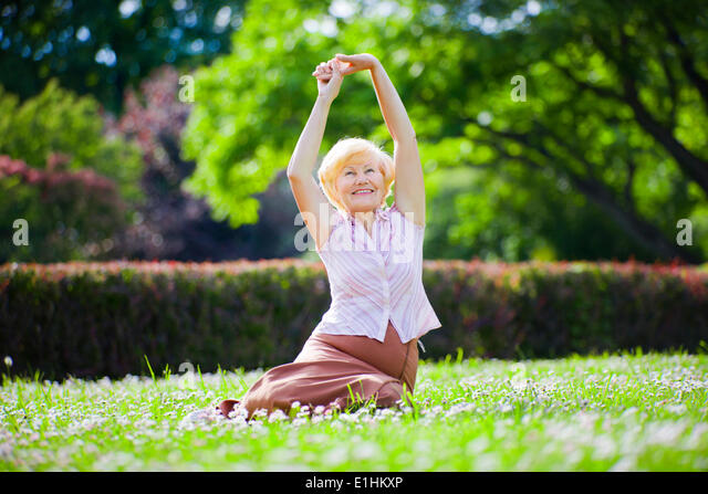 Wellness. Psychische Gesundheit. Optimistische alte Frau trainieren unter freiem Himmel Stockbild