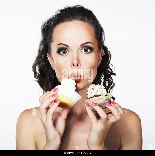 Völlerei. Hungrige lustige junge Frau gierig essen Kuchen mit Sahne Stockbild