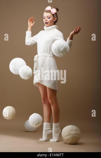 Fallende Stränge. Überrascht Frau in Woolen Jersey mit weißen Kugeln Garn gestrickt Stockbild