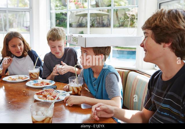 Junge Ausgleich Pizzakarton auf Kopf Stockbild