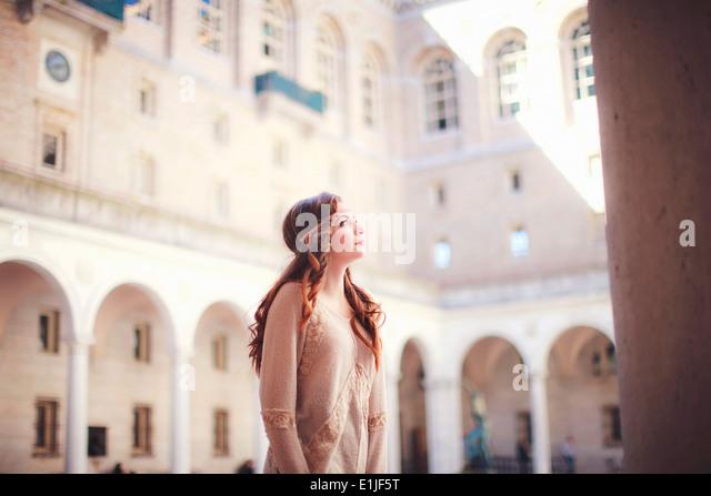 Junge Frau blickte im historischen Innenhof Stockbild