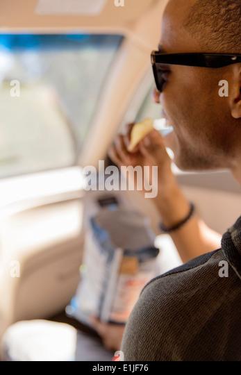 Nahaufnahme des jungen Mannes lesen Naschen auf Chips im Auto Stockbild