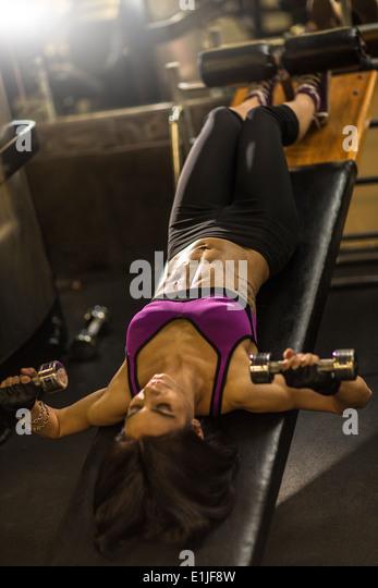 Mitte Erwachsene Frau tut Bauch-Übung auf der Hantelbank Stockbild