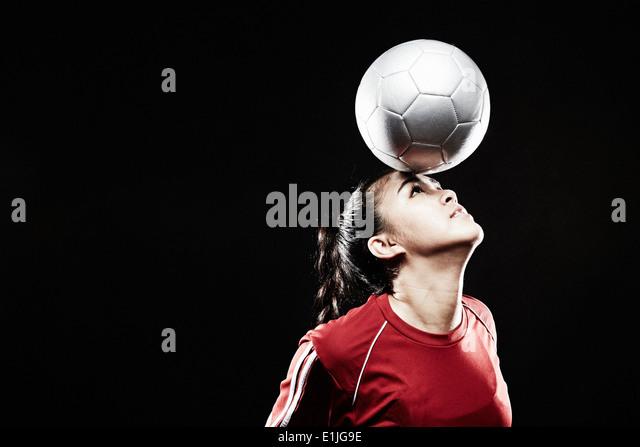 Junge Frau balancieren Fußball auf Stirn Stockbild