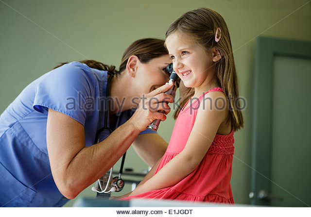Kinderarzt in des Mädchens Ohr suchen Stockbild
