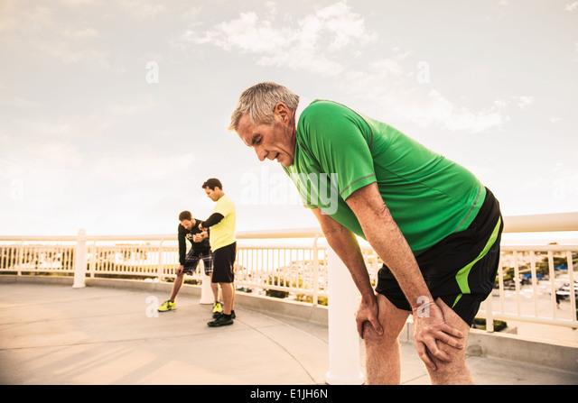 Erschöpfte männliche Läufer, die eine Pause vom training Stockbild