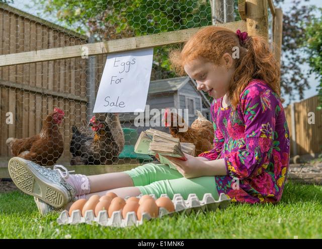 Kleine Mädchen Unternehmer sitzt mit Tausende von Pfund, während Hennen Eiern verkaufen. Stockbild