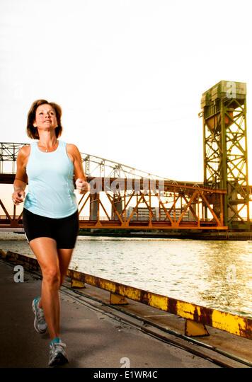 Attraktive Frau in ihrem 50 ist auf einen urban Trail Joggen. Stockbild