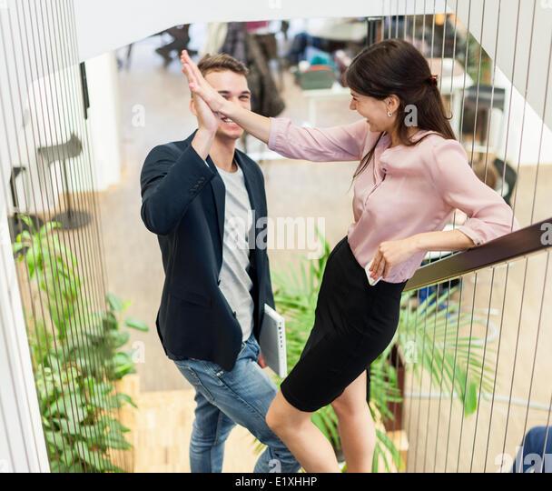 Voller Länge von Jungunternehmen paar tun High-Five auf Treppe Stockbild