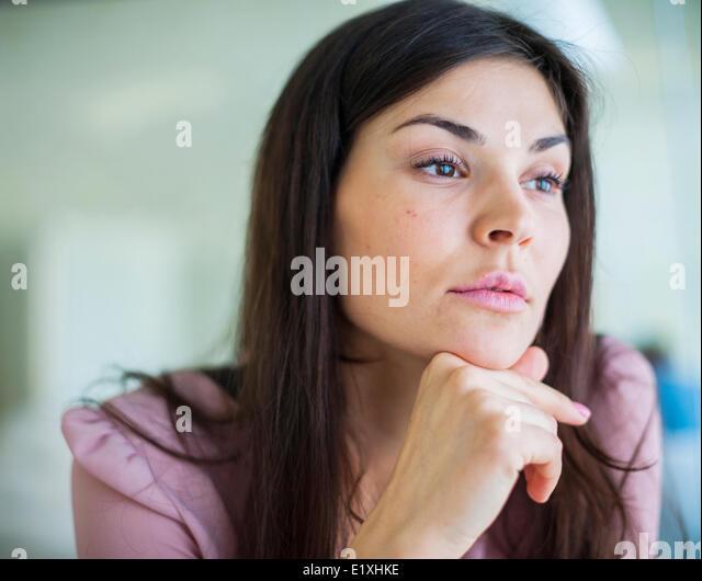 Nachdenkliche junge Geschäftsfrau wegschauen im Büro Stockbild
