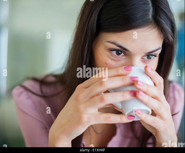 Junge Geschäftsfrau mit Kaffee in Büro Stockbild