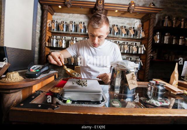 Männliche Besitzer Messung Zutat auf Waage im Teeladen Stockbild