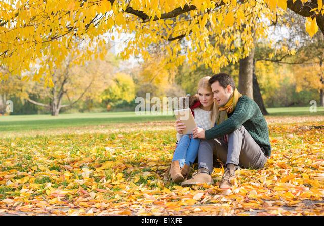 Voller Länge von paar mit tablet-PC im Park im Herbst Stockbild