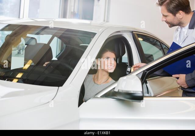 Kundin empfangenden Autoschlüssel von Mechaniker in Automobil-Werkstatt Stockbild