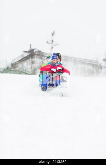 Gruppe von Freunden genießen Schlittenfahrt im Schnee Stockbild