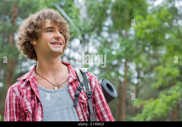 Lächelnd männlichen Wanderer wegschauen im Wald Stockbild