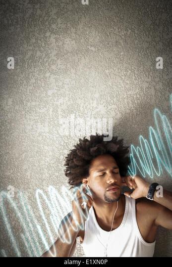 Entspannte junger Mann Musik hören während Sie lehnen an Wand Stockbild