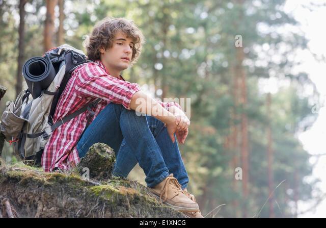 Voller Länge der nachdenklichen männlichen Backpacker entspannend auf Felsen im Wald Stockbild