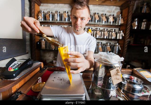 Verkäufer, die Aushöhlungen Zutat in Papiertüte im Teeladen Stockbild