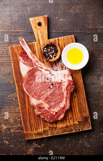 Rohes Frischfleisch Ribeye Steak mit Gewürzen und Öl auf Holz dunkel Stockbild