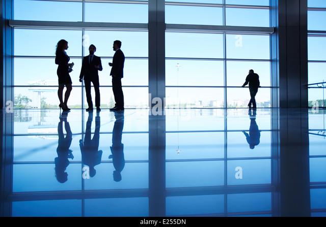Silhouetten von mehreren Büroangestellte am Fenster stehen und reden Stockbild
