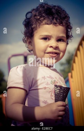 Kleinkind (2-3) auf Spielplatz beim Essen ein Eis Stockbild