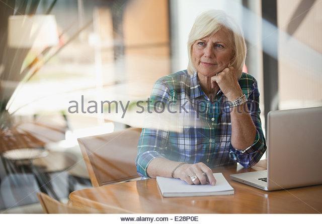 Ältere Frau mit Laptop im Haus Stockbild