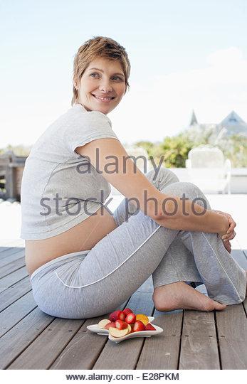 Schwangere Frau sitzen an deck Stockbild