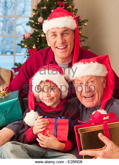 Mehr-Generationen-Familie Santa Hüte trägt und hält Weihnachtsgeschenke Stockbild