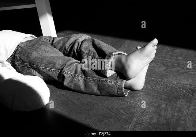 Kind mit am Knöchel, beschnitten, gekreuzten Beinen am Boden liegen Stockbild
