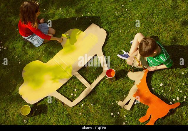 Kinder malen Karton Cut Outs im Garten Stockbild